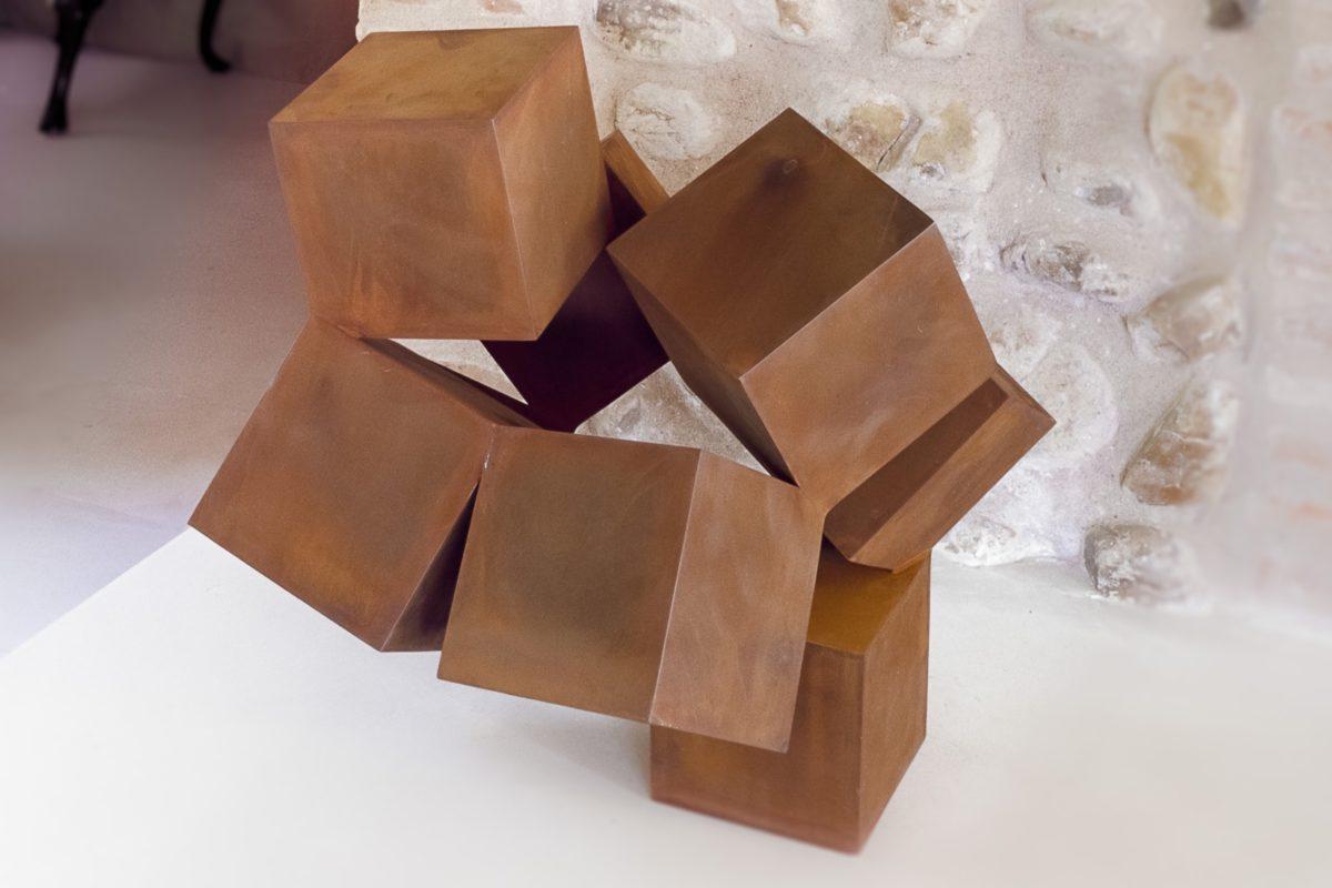 Escultura compuesta de diferentes cubos hechos de acero corten y acabado oxidado