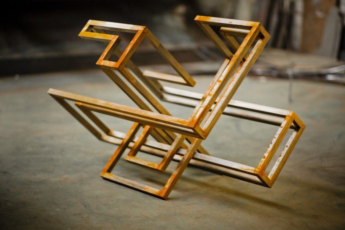 Escultura hecha con barras de acero corten de sección cuadrada