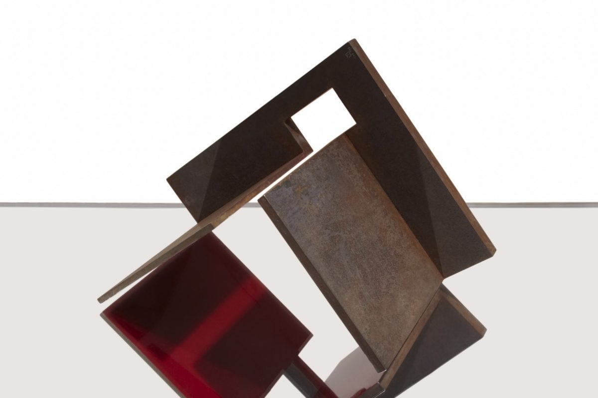 Oxidized corten steel sculpture with partially red lacquered finish