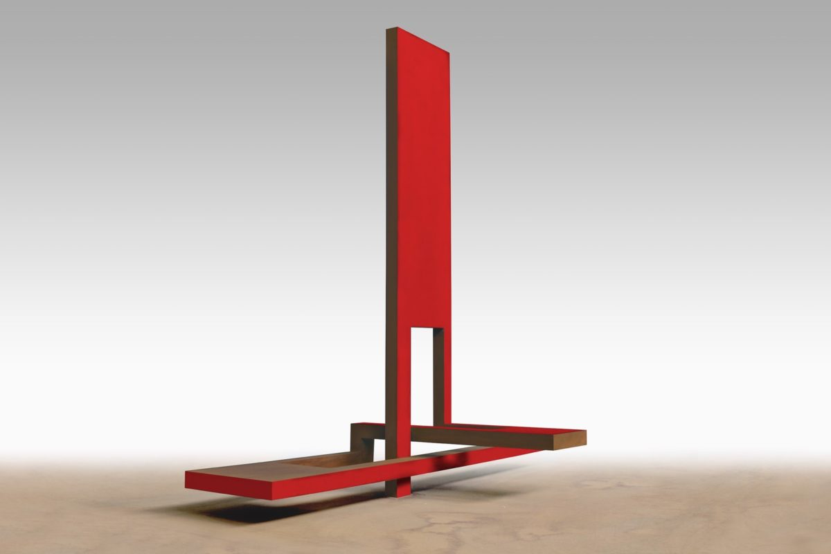 Corten steel sculpture shaped like a sail and with a partially red lacquered finish