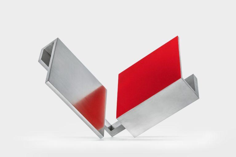 Escultura geométrica en acero pulido y parcialmente lacada en rojo