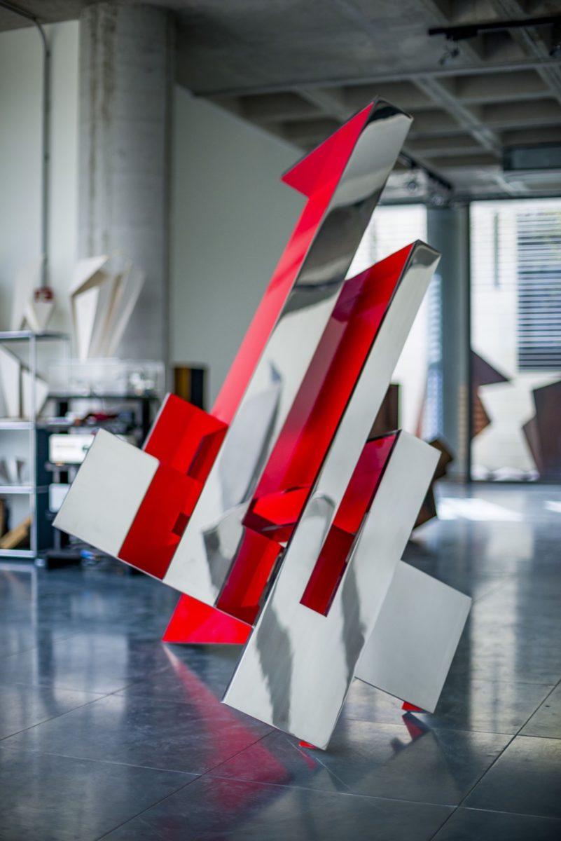 Escultura de acero inoxidable con acabado espejo y parcialmente lacada en rojo